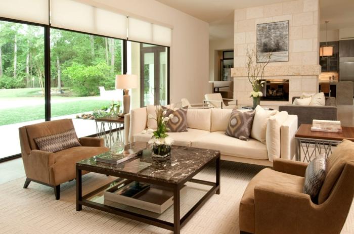 wohnzimmermöbel landhausstil moderne ideen für die wohnung am stadtrand, große fenster quadratischer tisch mit blumen darauf, sessel, sofa, kaminofen, wandbilder