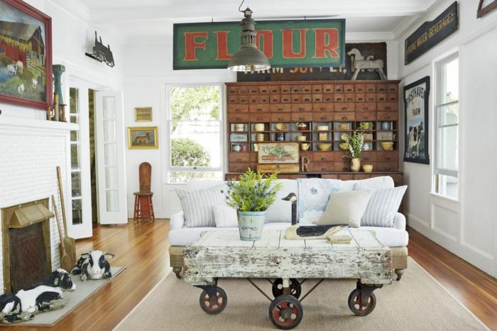 kreative wohnzimmer deko idee, tisch mit rollo beine, kaminofen, zwei keramikfiguren kühe, cooles design