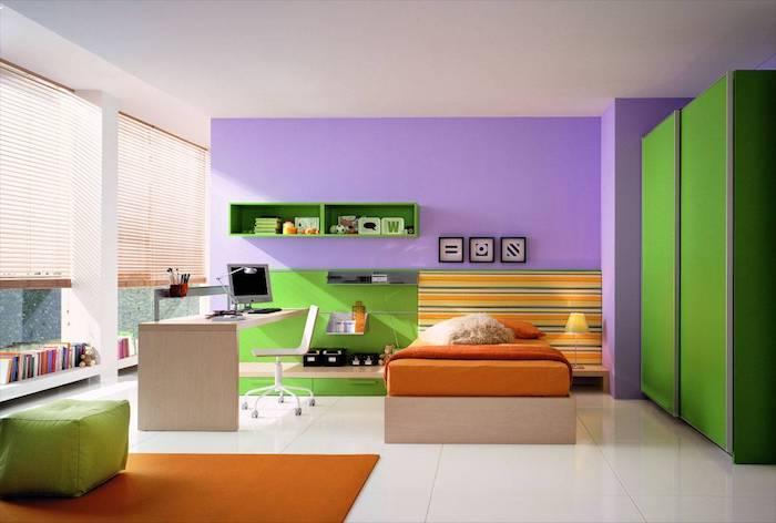 eine große violette wand mit drei bildern und grünen regalen, ein oranges bett und ein schreibtisch aus holz und ein stuhl, kinderzimmer einrichten, wandfarbe schlafzimmer