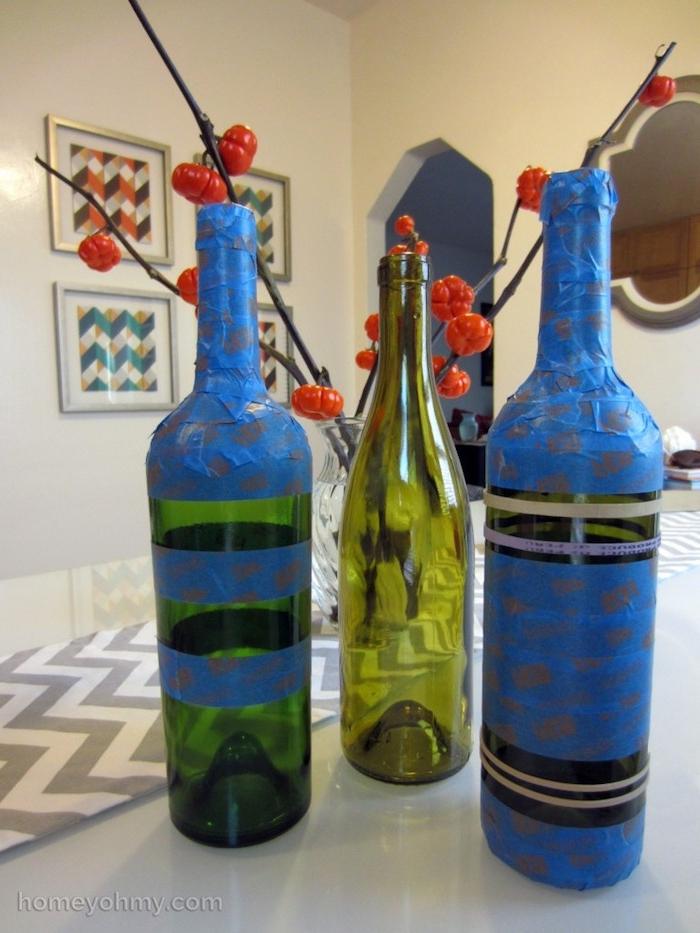 eine tischdekoration mit zwei blauen alten weinflaschen und mit einer grünen flasche aus glas, vasen aus flaschen selber machen