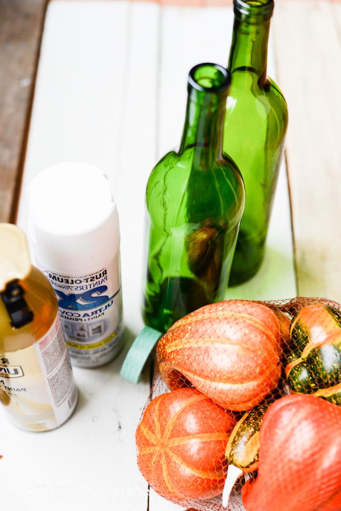 kleine orange kürbisse und zwei grüne flaschen aus glas und ein weißer tisch aus holz, basteln mit flaschen, diy ideen