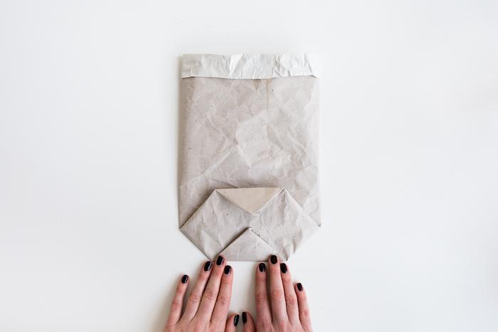 ein weißer tisch und eine kleine gefaltete alte weiße papiertüte und zwei hände mit einem schwarzen nagellack