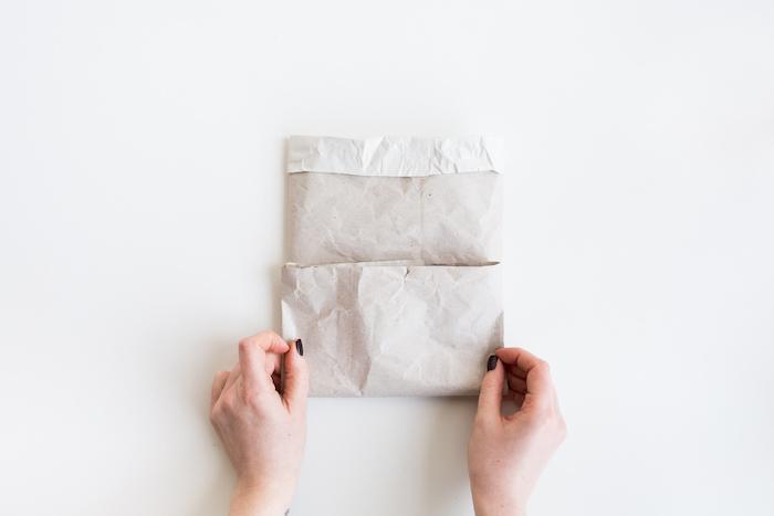 kleine weiße papiertüte und ein weißer tisch und zwei hände mit einem schwarzen nagellack, geschenke selber basteln ideen, eine diy schritt für schritt anleitung