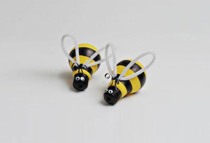 zwei kleine gelbe bienen mit schwarzen augen und mit grauen flügeln und aus zwei bemalten alten glühbirnen