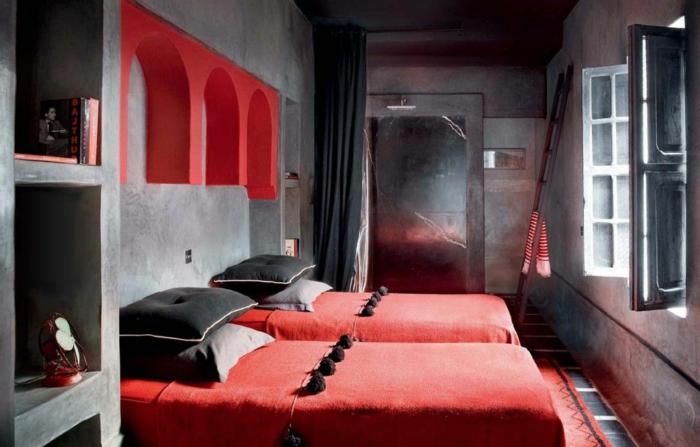 zwei Betten mit roten Decken, schwarze Kissen, Schlafzimmer in grauer Farbe