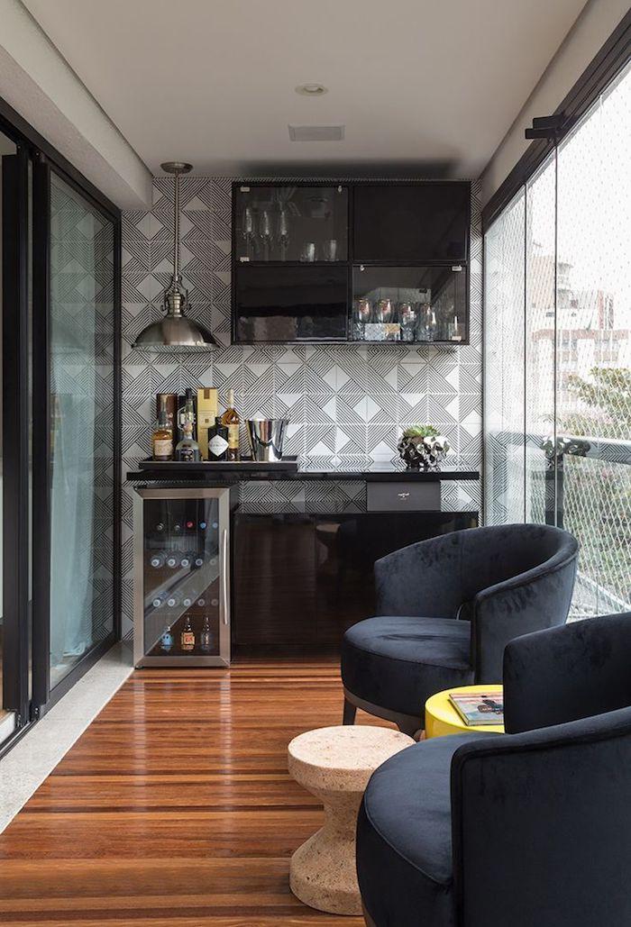 ein brauner boden aus holz, sessel und ein kleiner tisch, eine terrasse mit einer schwarzen miniküche