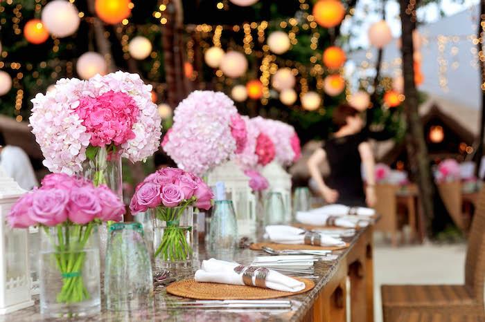 hochzeitstischdeko für hochzeit im sommer, glasvasen mit rosen, rosa hortensieren, lichterketten