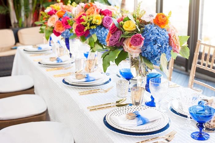 hochzeitstischdeko in bunten farben, blaue weingläser, goldenes geschirr
