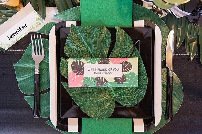 Tischdekoration in Grün, großes Blatt unter dem Teller, kleineres Blatt darauf, weiße Tischkarte