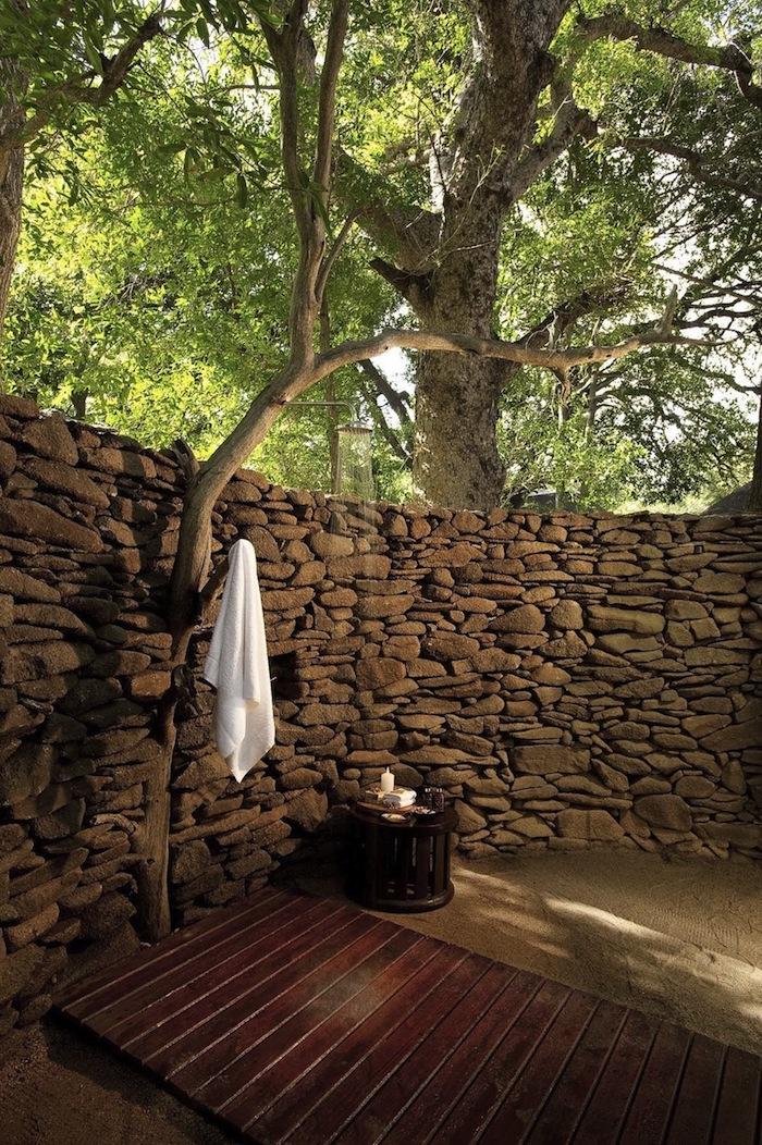 brauner boden aus holz im garten mit einer dusche, bäumen und wänden aus steinen, sichtschutz für gartendusche