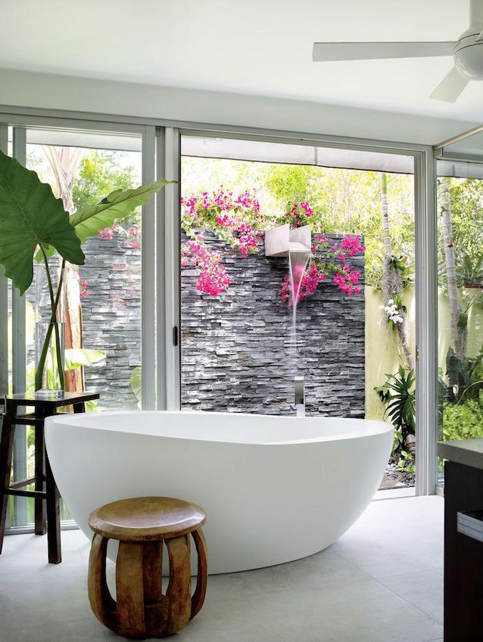 kleiner brauner stuhl aus holz, eine weiße kleine badewanne in einem haus mit garten und gartendusche, wand mit schwarzen steinen und grünen pflanzen und violetten blumen