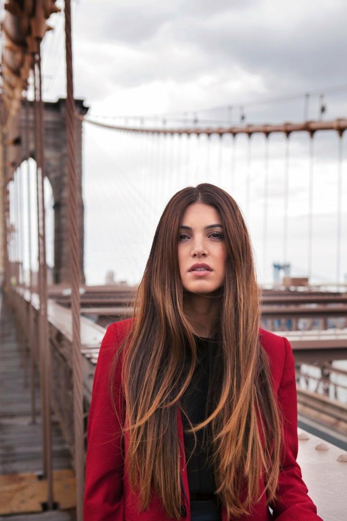 Lange und glatte Balayage Haare, schwarzes Top und roter Mantel, matter Lippenstift und leichtes Tages Make-up