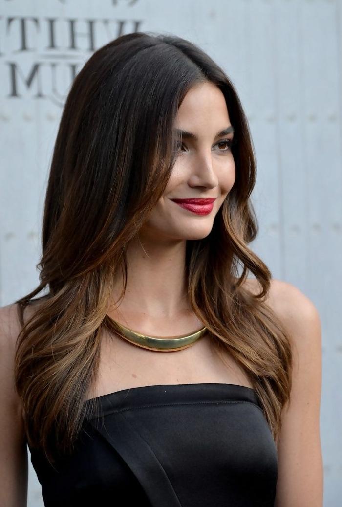 Ombre Braun Haarfarbe, lange wellige Haare mit Mittelscheitel, schwarzes trägerloses Kleid, massiver goldener Schmuck und roter Lippenstift