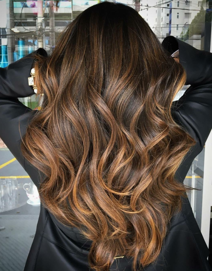 Lange und wellige Balayage Haare, Haarfarbe Karamell, schwarzer Blazer, goldenes Armband mit Kristallen