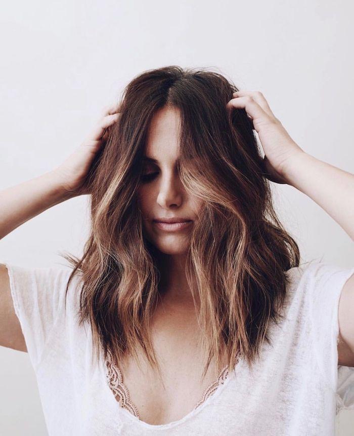 Dunkelbraune Haare mit Highlights, mittellange Haare mit Mittelscheitel, heller Hautteint und matter Lippenstift, weißes Top