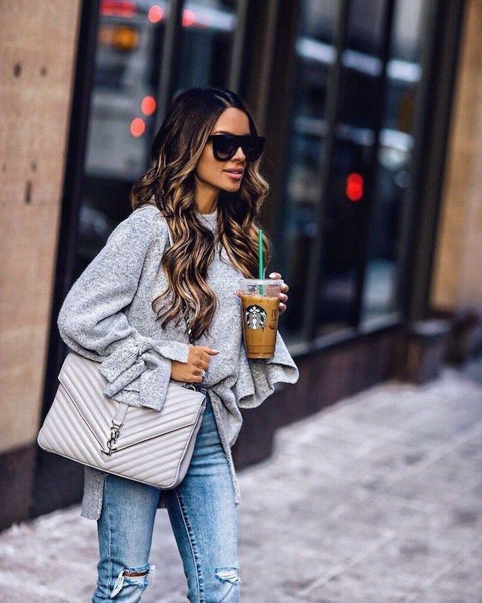 Lange dunkelbraune Haare mit blonden Strähnen, graue Bluse mit langen Ärmeln und Jeans