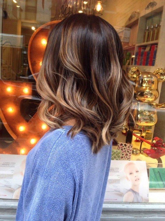 Mittellange dunkelbraune Haare mit blonden Strähnen, welliges Haar, hellblaue Bluse mit langen Ärmeln