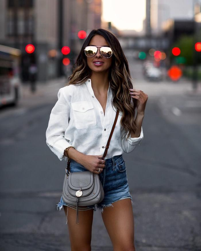 Lange Balayage Haare, weißes Hemd mit langen Ärmeln und Denim Shorts, graue Ledertasche