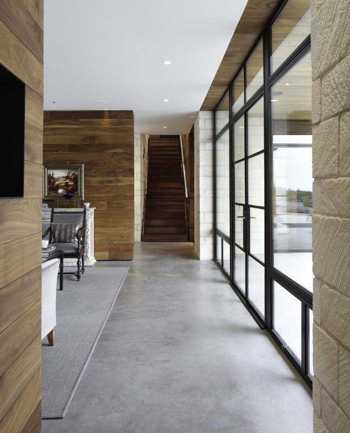 ein schmaler Flur, eine Glaswand mit schwarzen Rahmen, grauer Teppich, Betonboden, Deckenleuchten