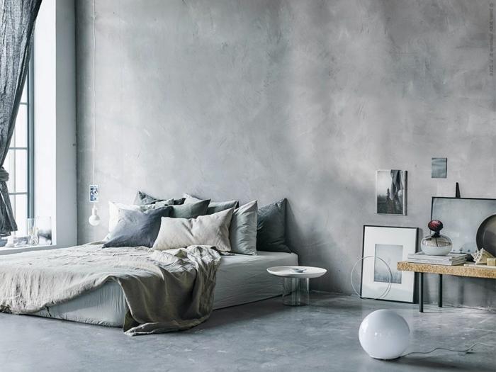 Schlafzimmer mit Betonboden, graue Wände, eine graue Matratze und graue Bettwäsche