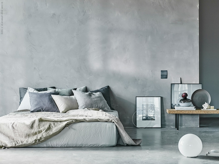 Schlafzimmer mit Betonboden, eine graue Matratze, kleine Dekorationen auf dem Tisch