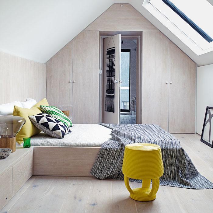 bett unter dachschräge, gelber hocker, dekokissen mit geometrischen mustern, boden aus holz
