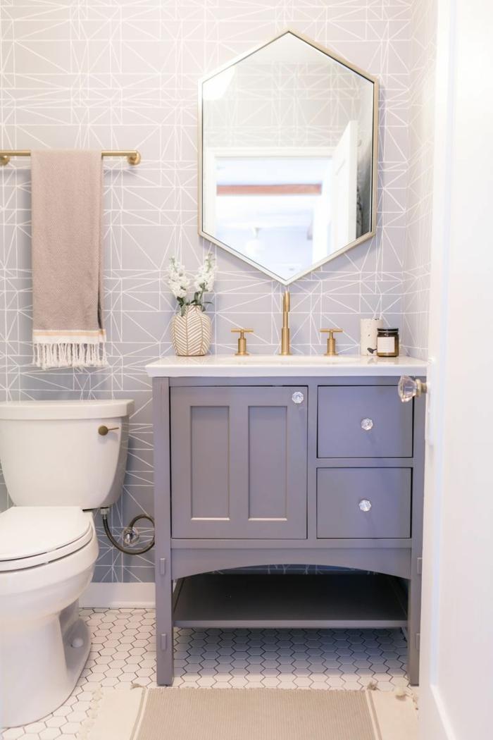 ein schöner Spiegel, blaues Bademöbel Set, ein kleiner beiger Teppich, weiße Mosaikfliesen, kleines Bad gestalten
