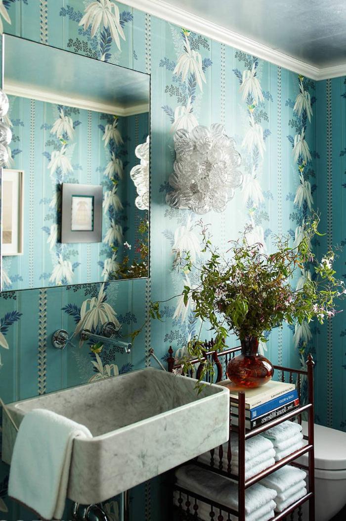 blaue Wand mit weißen Blumen als Muster, ein graues Waschbecken, kleines Bad gestalten