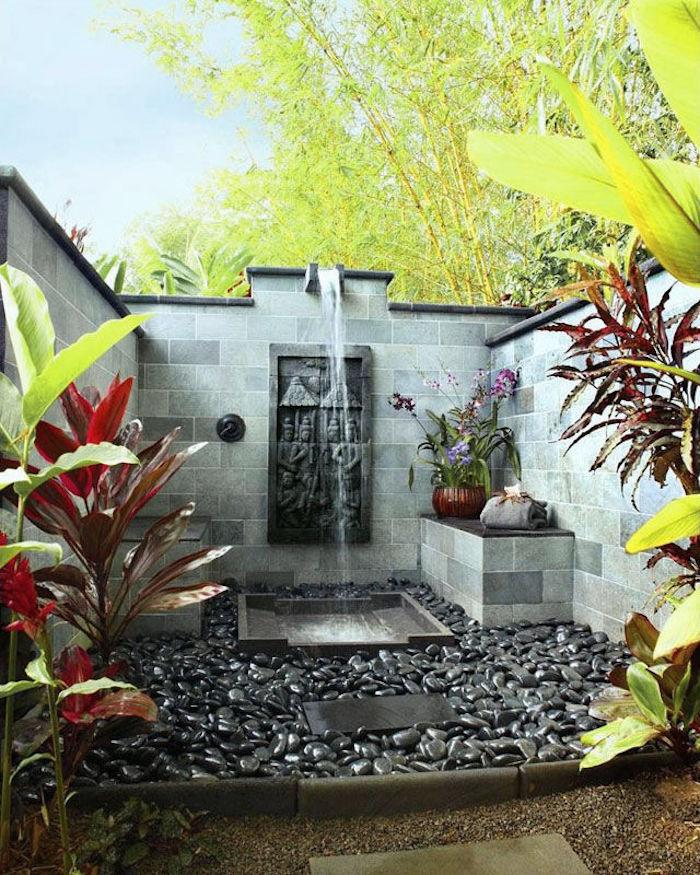gartengestaltung ideen, ein garten mit vielen grünen pflanzen und einer dusche, sichtschutz für gartendusche, gartenweg aus schwarzen und grauen steinen