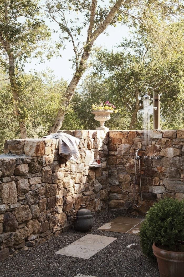 wand aus steinen in einem garten mit grünen bäumen und braunen und weißen blumentöpfen mit grünen und violetten pflanzen, sichtschutz für gartendusche selber bauen