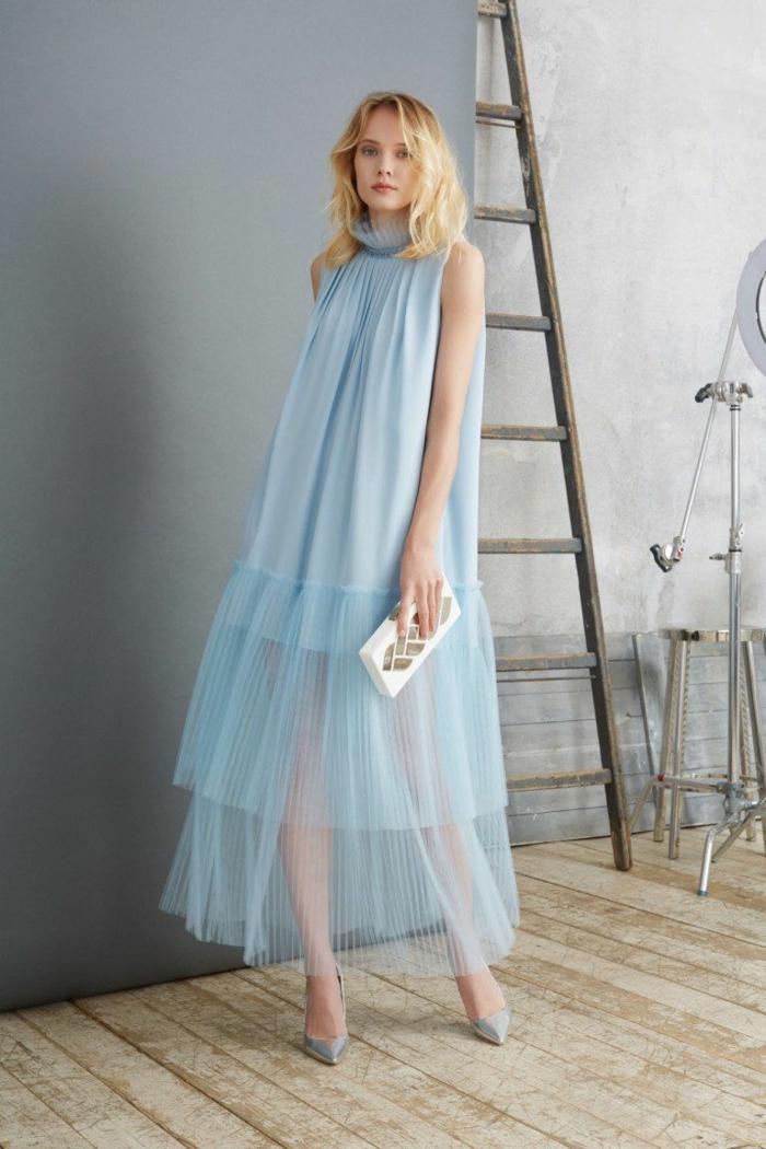 blaues Kleid von einer blonden werdenden Mutter, festliche Kleider für Schwangere, kleine weiße Tasche