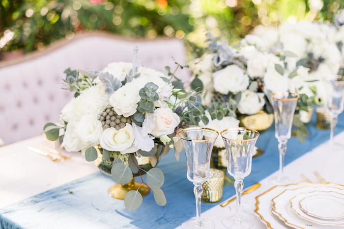 blauer tischläufer, blumengestecke hochzeit, weiße rosen, weingläser mit goldenen elementen