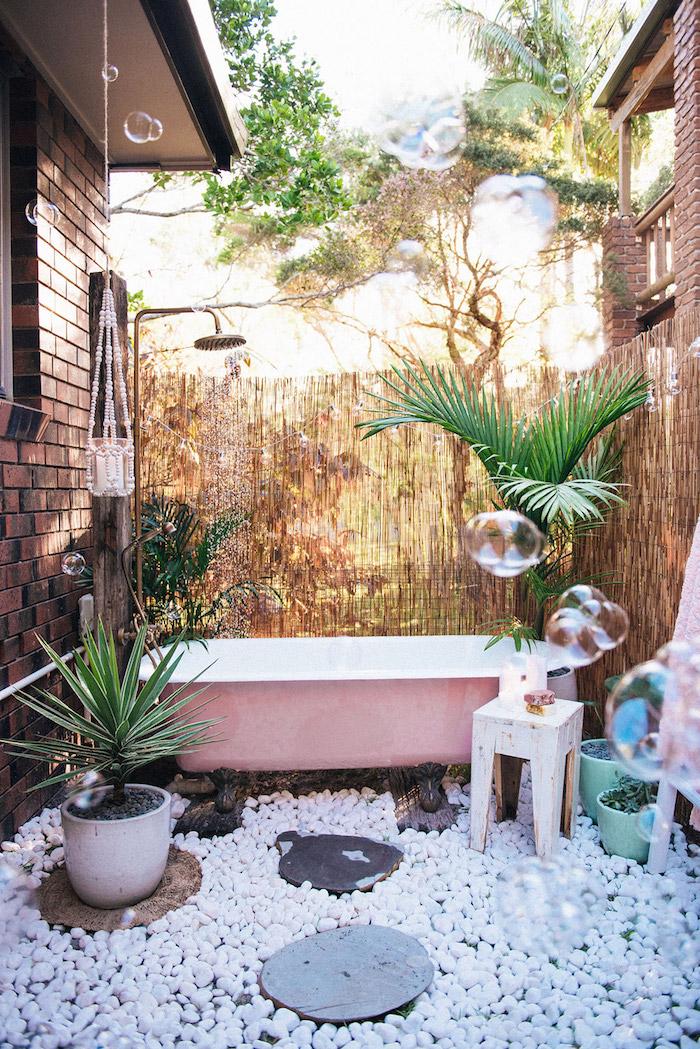 weißer boden aus vielen kleinen weißen steinen, eine kleine pinke badewanne im garten mit grünen pflanzen und gartendusche