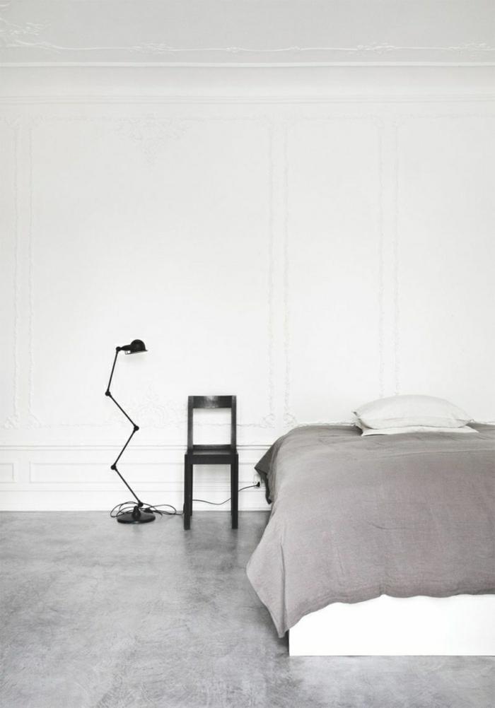 eine weiße Wand, Betonboden, eine graue Decke, ein schwarzer Stuhl, eine schlichte Einrichtung