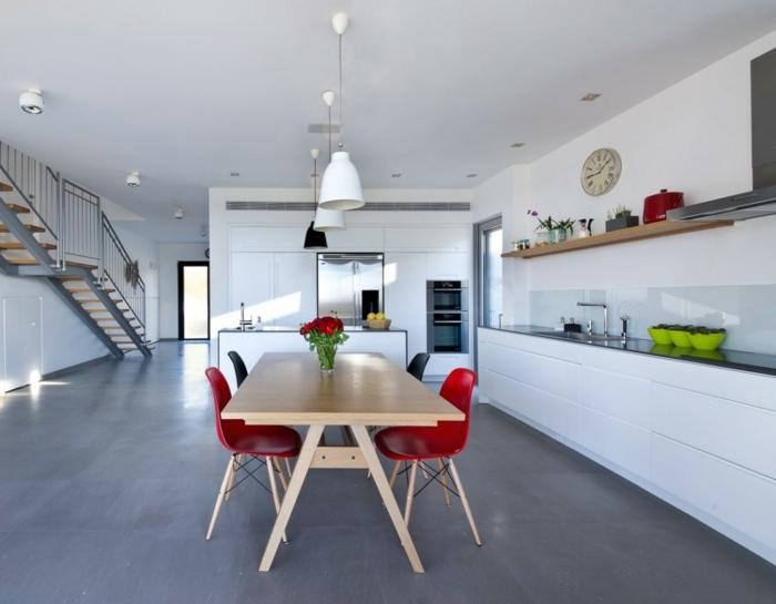 ein brauner Tisch, vier bunte Stühle, Pendelleuchte, eine Uhr an der Wand, Betonboden
