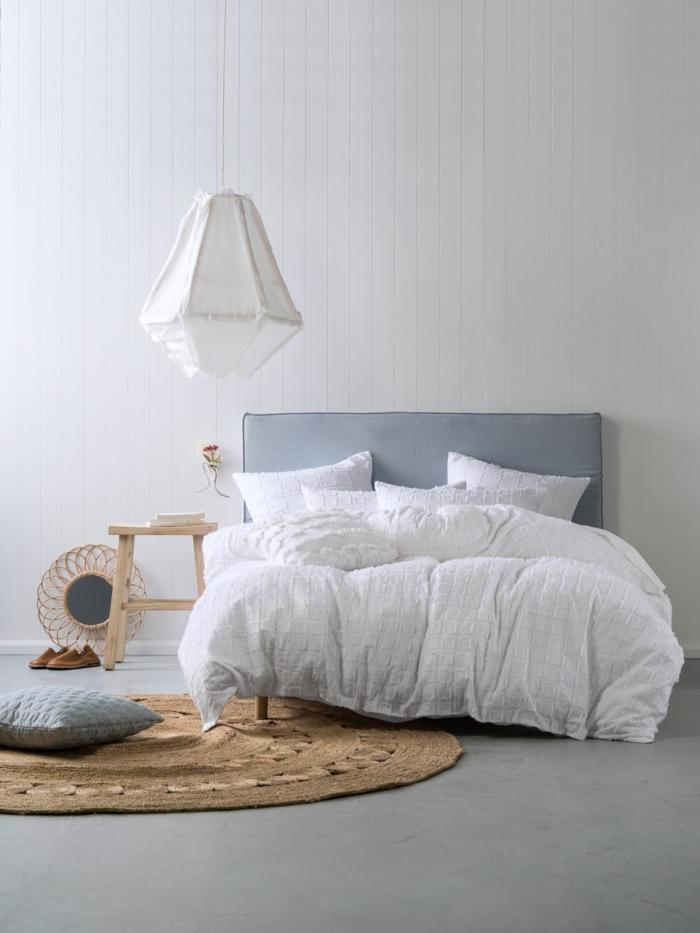 Betonboden, ein ausgefallener Lampenschirm, Bett mit weißen Bettwäschen, ein kleines Stühlchen