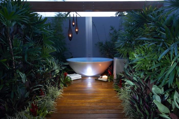garten mit grünen pflanzen und blättern und einer gartendzusche, brauenr boden aus holz und eine weiße badewanne mit gartendusche