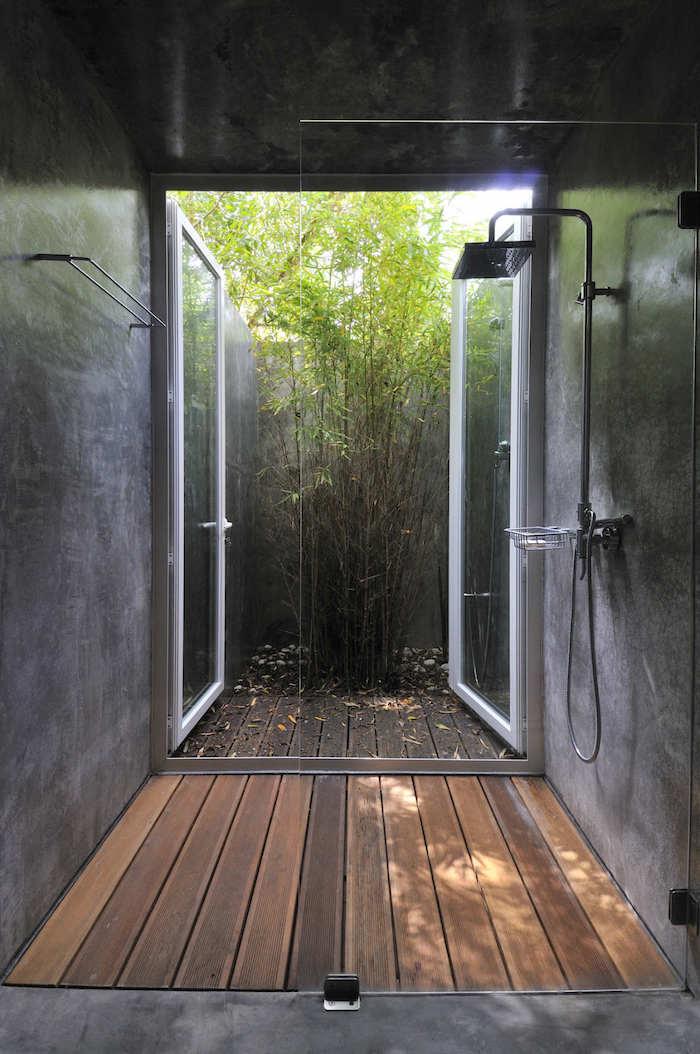 graue wände und eine gartendusche edelstahl, haus mit garten mit vielen ygrünen pflanzen und grünen blättern, brauner boden aus holz, gartengestaltung ideen diy