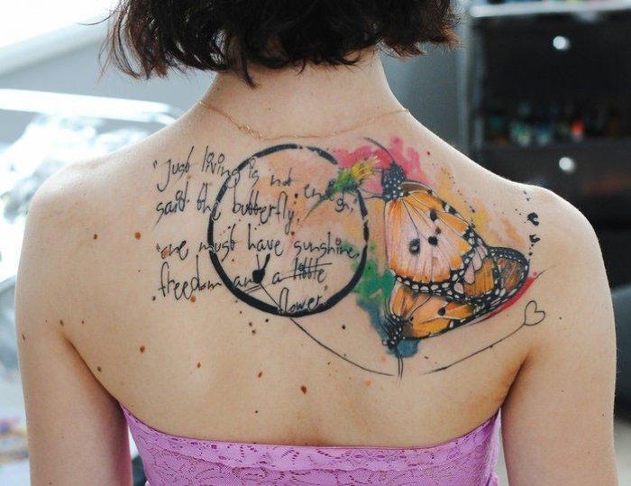 gedenk tattoo, frau mit farbiger tätoiwerung am rücken, schmetterlingflügeln in kombination mit spruch
