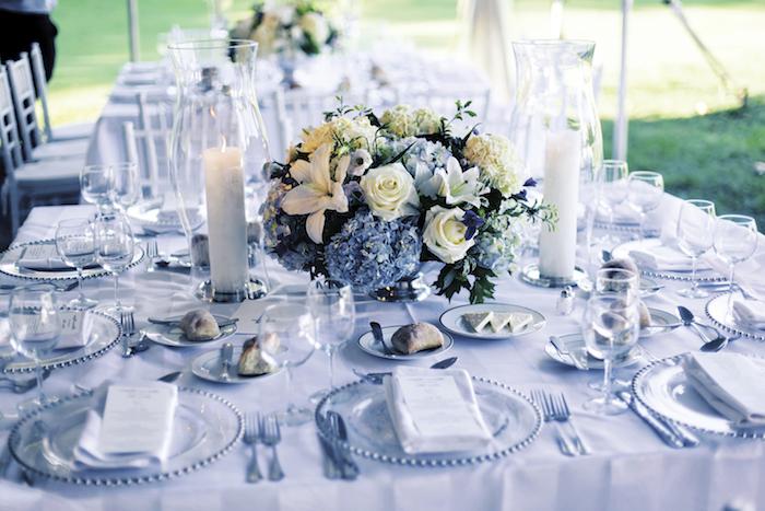 deko hcohzeit in blau und weiß, hohe kerzen, kerzenhalter aus glas, rosen, hortensien und lilien