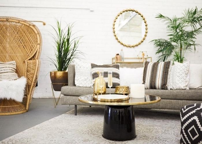 design wohnzimmer, goldener tisch, schwarz, rattan sessel, spiegel, grüne pflanzen