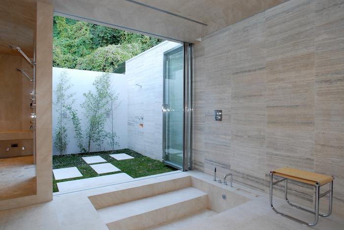 gartenweg aus weißen fliesen. haus mit einer weißen badewanne, garten mitn grünem rasen und einer gartendusche
