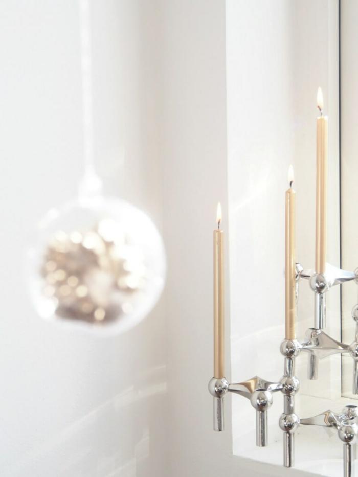 Basteln mit Kastanien, ein Kugel mit Kastanien in goldener Farbe und drei Kerzen auf Kerzenständer