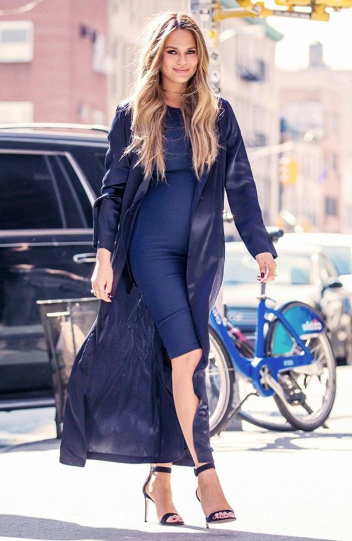 ein blaues Kleid, ein Mantel, schwarze Schuhe mit hohen Absatz, blonde schwangere Frau