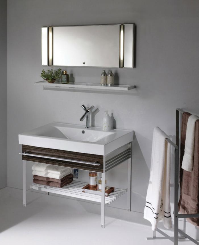 ein länglicher Spiegel, eine Leiste mit kleinen Dekorationen, schöne Badezimmer, ein weißer Waschbecken