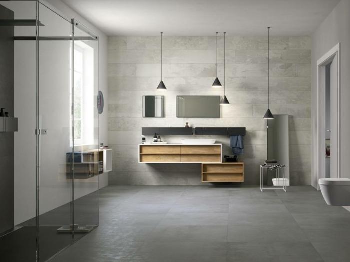 ein großes, gemütliches Badezimmer mit Pendelleuchten, viele Regalen, zwei Spiegel, Betonboden