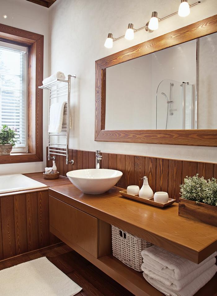 ein großer Spiegel mit indirekter Beleuchtung, ein rundes Waschbecken, schöne Badezimmer aus Holz