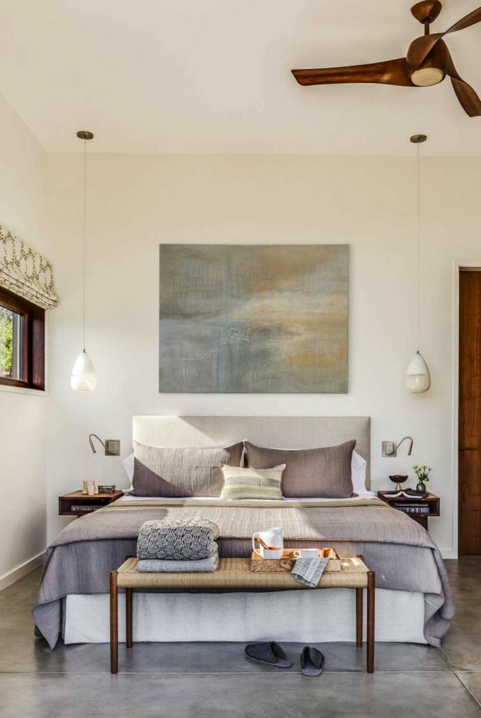 ein gemütliches Schlafzimmer, lila Bettdecke, Betonboden, zwei Pendelleuchten, zwei Nachttische