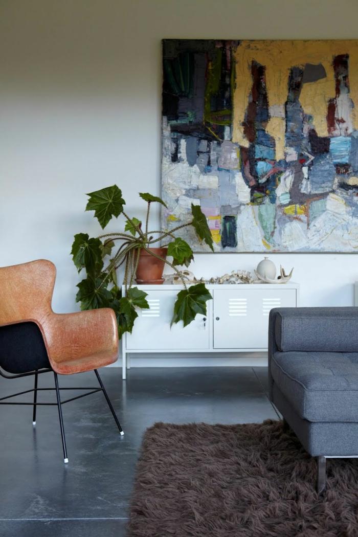 ein brauner Teppich, ein brauner Stuhl, Betonfußboden, ein weißes Regal, ein Blumentopf