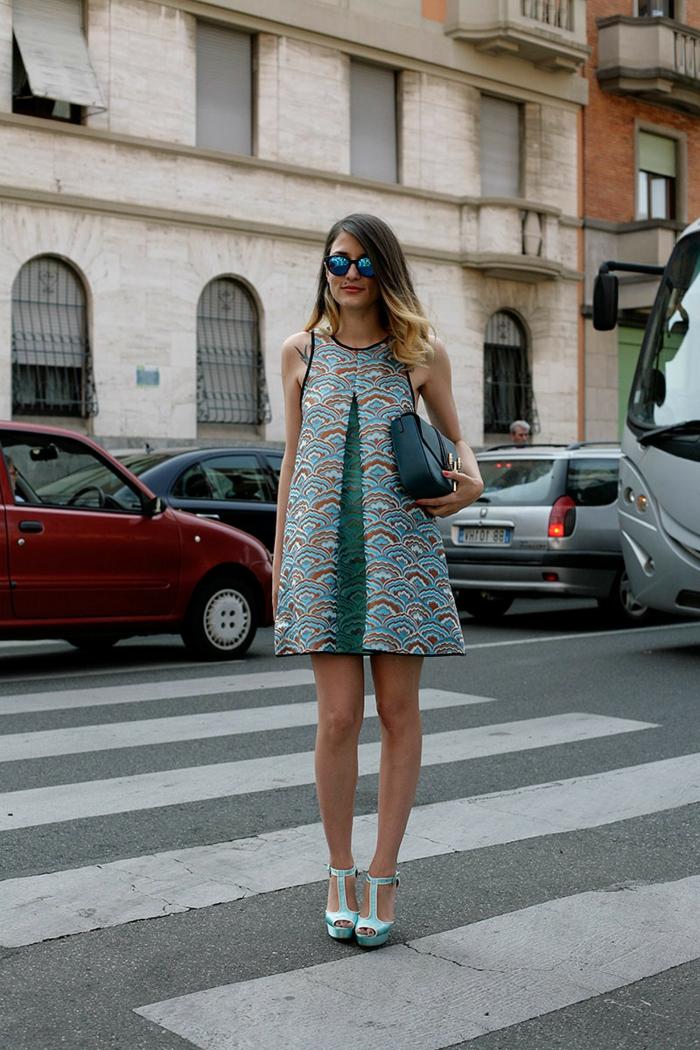 ein blaues Kleid mit Muster von Wolken, schwarze Sonnenbrillen, blaue Sandalen, eine blaue Damentasche, festliche Kleider für Schwangere